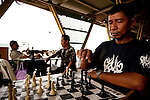 Men play chess at a market in Kota Kinabalu, Sabah, Malaysia.