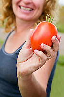 Ontario farmer Kim Delaney shows off a ripe plum tomato that she grows for seeds for Urban Harvest.