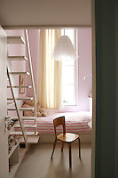 The 'tutu' style light shade is a charming feature of this girl's bedroom in which an open staircase leads to a mezzanine