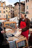 Vendor selling freshly baked bread from biodynamic wheat and grains, at street side market on Vicolo della Moretta, Rome, Italy