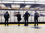 People standing on a platform, waiting for a subway train to arrive. Toronto TTC, Ontario, Canada.