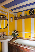 In the bathroom a striped effect is created with walls painted yellow and woodwork picked out in white