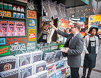 "Eric Mueller buys a magazine at ""T. SQ Newsstand"" in Times Square in New York on Friday, October 9, 2015. Created by the artist Kimou ""Grotesk"" Meyer with Victory Journal and Juxtapoz Magazine, the pop-up displays and sells art and culture zines created by a litany of artists. It will be in business at the crossroads of the world until October 18. (© Richard B. Levine)"