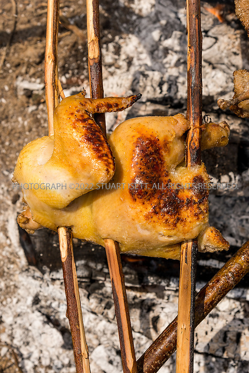 6/22/2015 &mdash; Everett, WA, USA<br /> <br /> Steven Rinella, an avid outdoorsman and hunter, cooks both wild duck and domesticated chicken over an open wood fire in Everett, WASH. Both birds were skewered with branches cut from nearby Alder trees and hung over the fire using more Alder branches.<br /> <br /> Here the chicken turns godlen brown.<br /> <br /> Photograph by Stuart Isett<br /> &copy;2015 Stuart Isett. All rights reserved.