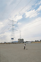 A boy plays football alone under enormouse electricity towers. Toluca, Mexico, March 20, 2006. Football llanero, which translates  as street football being played as the build up for the 2006 world cup approaches its peak