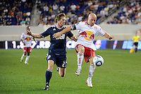 Luke Rodgers (9) of the New York Red Bulls plays the ball under pressure from Jonathan Leathers (25) of the Vancouver Whitecaps. The New York Red Bulls and the Vancouver Whitecaps played to a 1-1 tie during a Major League Soccer (MLS) match at Red Bull Arena in Harrison, NJ, on September 10, 2011.