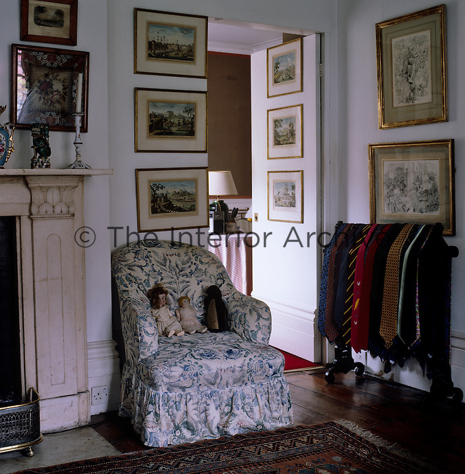 In the bedroom a velvet toy-penguin and two antique dolls sit in an armchair upholstered in fabric by Oliver Messel