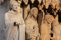 Statues of an apostle, woman and angel, restored 1821-47 under Auguste Cheussey, by the sculptor Theophile Caudron, on the embrasures of the central portal, known as the Beau-Dieu portal, dedicated to the Last Judgment, on the Western facade of the Basilique Cathedrale Notre-Dame d'Amiens or Cathedral Basilica of Our Lady of Amiens, built 1220-70 in Gothic style, Amiens, Picardy, France. The ommission of several attributes when replacing the statues means the apostles are now difficult to recognise. Amiens Cathedral was listed as a UNESCO World Heritage Site in 1981. Picture by Manuel Cohen