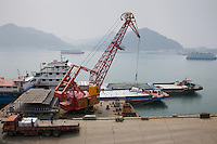 Loading dock crane lifts aluminim ingot blocks onto cargo ship, Yichang, China