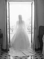 back of a woman in a beautiful wedding dress walking out to a balcony bathed in light
