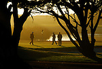 Golfers in Pacific Grove at sunset