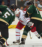 1/28/05  Omaha, NE University of Nebraska at Omaha's Bill Bagron maneuvers between Wayne StateÕs Mark Nebus and Steve Kovalchik                                . (photo by Chris Machian/ Prarie Pixel Group)