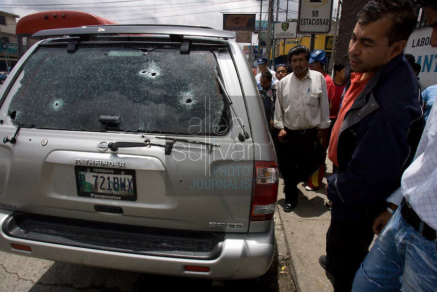 People look at an automobile in Guatemala City, Guatemala in which two people were shot to death the previous night. Local papers said the two were killed by about six gunmen who shot more than 120 rounds into the car. It was said to be an assassination connected to the narcotics trade.
