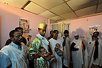 Eritrean asylum-seekers pray before conducting a baptism ceremony for two babies, at a side room of their makeshift church in southern Tel Aviv, Israel, where a former brothel was operated.