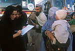 A UN worker checks who gets on the buses taking Afghan refugees from the squalid camp at Jalozai to a new camp closer to the border with Afghanistan..