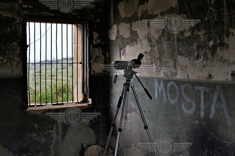 A spotting scope placed inside a derelict building.Under EU leglislation, hunting or trapping birds in spring is illegal but the government of Malta, which joined the EU in 2004, allows hunting of turtle dove and quail at this time of year. Some 170 species of bird pass over Malta during the spring and autumn migration periods. Hunters regularly shoot other species including birds of prey which are stuffed for private collection. Spring Watch Malta is a conservation camp run by BirdLife Malta, a non-profit which lobbies against bird hunting in the country. In 2012, fifty volunteers from across Europe converged on a tourist hotel in Bugibba in northern Malta and fanned out to track migrating birds and monitor any illegal spring hunting by the 11,000 permitted hunters....