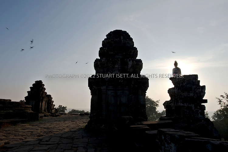 11/28/2008--Siem Reap, Cambodia..A young Cambodian woman meditates at dawn on the ninth-century Phnom Bakheng in the Angkor Archaeological Park.The five-tiered structure is one of the park?s temple mountains, so-called because they?re modeled on Mount Meru, the mythological home to Hindu gods. (Buddhism would later take over as the primary religion.) What this means is that you?ll have to work for the view: It?s a 15-minute hike up to the sandstone terrace, which overlooks an endless expanse of jungle and mist-covered hills. ..©2008 Stuart Isett. All rights reserved.