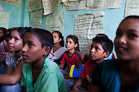 Ganga Regmi (pink), 10, attends a club meeting at the Kishuri Sachetana Child Club in their activity center in Thahuri Tole, Chhinchu, Surkhet district, Western Nepal, on 1st July 2012. Ganga's ambition is to be a doctor. 16-year-old Bhawani Regmi (in grey/pink) who is the president of the district level child forum, 11-year-old  Sarawati Regmi (in white), and 10-year-old Ganga Regmi (in pink) are daughters of pandit (Hindu priest) Dharma Raj Regmi who is one of the 3 priests who have agreed to stop solemnizing child marriages. These Child Clubs, supported by the government, Save the Children and their local partner NGO Safer Society, advocate for child rights and against child marriages and use peer support and education to end child marriages and raise awareness. Photo by Suzanne Lee for Save The Children UK