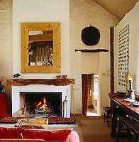 A log fire burns in the hearth of the cosy whitewashed living room which is decorated with an eclectic combination of furniture and items collected over years of travelling