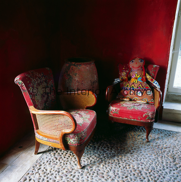 Two cane wood and cane chairs with floral upholstery stand in one corner of a red room, which has a stone cobbled floor.