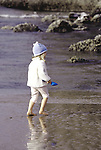 A girl with blue bear crochet hat on the beach carrying a shovel in Oregon.