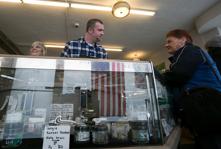 Budtender Wes McLeos (C) helps a customer at Main Street Marijuana in downtown Vancouver February 14, 2017. (Photo by Natalie Behring for the Columbian)