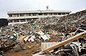 March 8, 2012, Minamisannriku-cho, Japan - A local school building is almost hidden behind a mountain of debris at Minamisannriku-cho, Miyagi Prefecture, some 365 km northeast of Tokyo, on Thursday, March 8, 2012. ..One year after the strongest earthquake ever to hit Japan, the economy is recovering and massive cleanup operations are in full swing throughout much of the countrys northeastern region. But once-pastoral landscapes that were piled with rubble and debris have become empty wastelands due mainly to bickering and disagreements between the central and local governments over rebuilding the devastated region. A year later, more than 260,000 people still live in temporary shelters. (Photo by Natsuki Sakai/AFLO) AYF -mis-.
