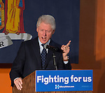 Elmont, New York, USA. April 5, 2016. Former President Bill Clinton, with an angry expression and pointing his index finger while giving a speech, is the headline speaker as he campaigns at an Organizing Event rally in Elmont, Long Island, on behalf of his wife, Hillary Clinton, the leading Democratic presidential candidate, and former Secretary of State and U.S. Senator for New York. Podium has 'Fighting for us' slogan on sign. The New York Democratic Primary takes place April 19th.