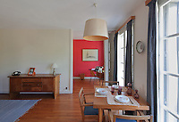 Living room with dining table and chairs by the windows, and study behind, in the Historic Show Flat, on the first floor of an ISAI or Immeubles Sans Affectation Individuelle apartment block, designed from 1946 by Auguste Perret, 1874-1954, who led the reconstruction of Le Havre in the 1950s, after the town was completely destroyed in WWII, Le Havre, Normandy, France. The apartment, of early 1950s design, used all modern conveniences, including internal kitchen and bathroom, contemporary mass produced oak furniture, natural light flowing from front and back, children's study bedroom, central heating and domestic appliances such as vacuum cleaners and refrigerators. Rene Gabriel and Marcel Gascoin designed the furniture in Scandinavian style, which came to typify reconstruction design. The centre of Le Havre is listed as a UNESCO World Heritage Site. Picture by Manuel Cohen