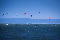 Kite surfing on San Francisco Bay with the colorful kites floating over the highrise portion of the San Mateo Bridge as viewed from Crown Beach in Alameda, California.