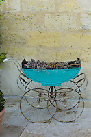 Antique traditional pram with dried grasses in St Emilion, Bordeaux, France