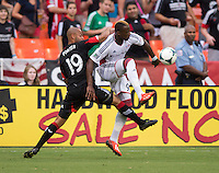 Dimitry Imbongo (92) of the New England Revolution fights for the ball with Kyle Porter (19) of D.C. United during a Major League Soccer game at RFK Stadium in Washington, DC.  New England defeated D.C. United, 2-1.