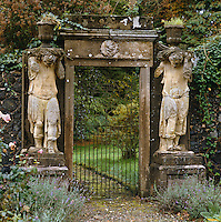A simple iron gate within an imposing stone entrance flanked by a pair of statues carrying urns leads into the garden