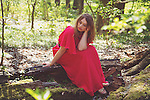 Thoughtful young woman sitting alone on a tree stump wearing a long red dress in summer