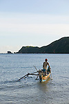 A fisherman takes his boat into the bay off Kuta beach, Lombok, Indonesia.