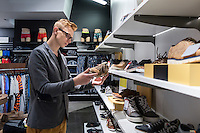 Young man looking shoes in retail shop Tartu Kaubamaja, Estonia. Shoes on shelves.