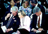 """Arlington, VA - (FILE) -- United States Senator Edward M. """"Ted"""" Kennedy (Democrat of Massachusetts), left, shares a thought with first lady Hillary Rodham Clinton, center, at a memorial service honoring his slain brother, former U.S. Senator Robert F. Kennedy (Democrat of New York) on the 25th anniversary of his assassination at Arlington National Cemetery on June 6, 1993.  At right, U.S. President Bill Clinton updates his remarks..Credit: Howard L. Sachs / CNP"""