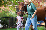 Mia Phillips joins Rosco the horse and its owner, Susen Cretekos, during a parade of animals.
