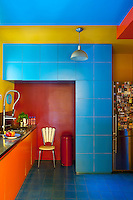 The kitchen is a fantastic array of bright colours from the blue floor tiles to the orange units and yellow walls