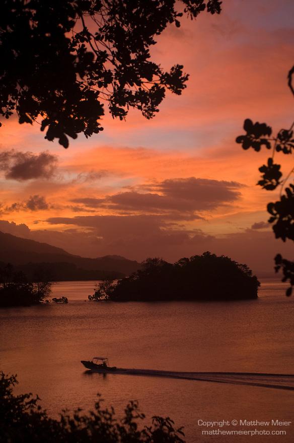 Milne Bay, Papua New Guinea; a speed boat drives past sunset views from Tawali Resort , Copyright © Matthew Meier, matthewmeierphoto.com