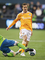Houston Dynamo defender Hunter Freeman tries to escape the slide tackle of a Seattle Sounders FC defender during play at Qwest Field in Seattle Friday March 25, 2011. The match ended in a 1-1 draw.