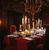 The stamped leather walls of the dining room glow in the light of the gilt candelabra on the damask-covered table