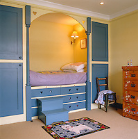 A child's niche bed is flanked by sets of cupboards and the mattress is placed above a series of drawers