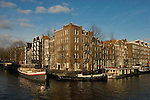 .Corner of Canal, Amsterdam, with barges and houseboats, new and old apartments.walshy@blather.net.+353872207023