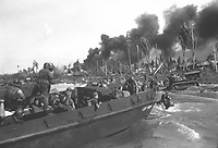 Australian troops storm ashore in the first assault wave to hit Balikpapan on the southeast coast of oil-rich Borneo.  Coast Guard Combat Photographer James L. Lonergan stands in the landing craft.  July 1945.  Gerald C. Anker.  (Coast Guard)<br /> Exact Date Shot Unknown<br /> NARA FILE #:  026-G-4718<br /> WAR &amp; CONFLICT BOOK #:  1171