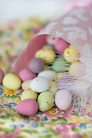 A paper cone is filled with small pastel coloured chocolate Easter eggs