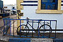 A blue bike leans against a blue railing in the coastal town of Essaouira, Morocco.