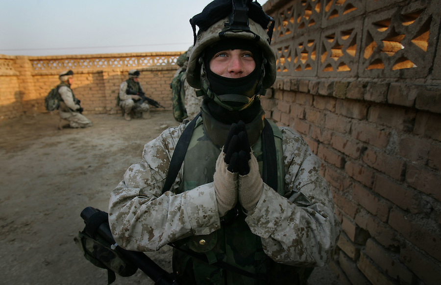 A Marine with 1st Platoon Golf Company 2nd Battalion 5th Marines offers up a half-joking prayer that the insurgents will attack their company as it searchs a cemetery and nearby park for hidden weapons caches on January 17, 2005 in Ramadi, Iraq. The search resulted in the discovery of several mortar rounds which were destroyed in place.