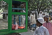 A reflection of a young boy is seen on a cart of pickles and goodies while other muslims from the Chowduli class seen coming out of the mosque after the friday prayers in Chaymalpur village of North 24 Parganas in West Bengal, India. Photo: Sanjit Das/Panos for The Wall Street Journal. Slug: ICASTE