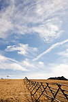 Crosses and gravestones are seen near a wooden fence and rocky hill on a warm spring day with clouds and a blue sky.
